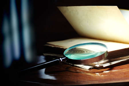 scientific literature: Old book and magnifier glass on a dark background as a symbol of knowledge and science