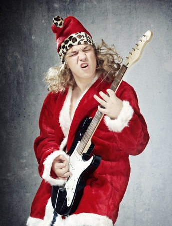 Man in the red and furry Santa Claus costume playing rock guitar on the grungy background Stock Photo - 8309386