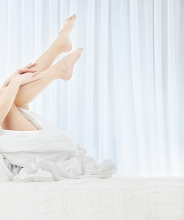 bedlinen: Sexy lady laying in the bed and making massage of her legs