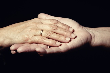 Two hands of senior people with engagement rings on a black background photo