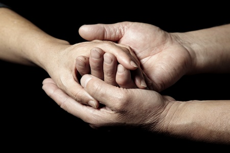 Hands of senior people supporting each other on a black background photo