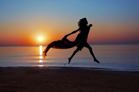 donna volante: Sagoma della donna battenti al mare durante il bellissimo tramonto. Luce naturale e darknesss. Aggiunta di colori vibranti