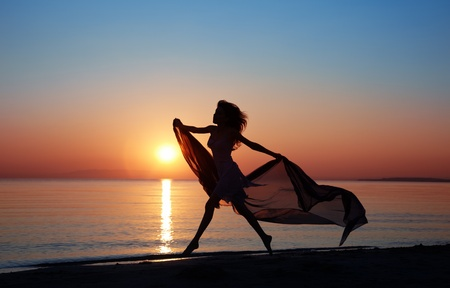 paradise: Silhouette of the happy woman with fiber dancing and jumping at the sunset beach