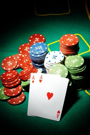 boodle: Pair of aces and poker chips on a green table in casino Stock Photo