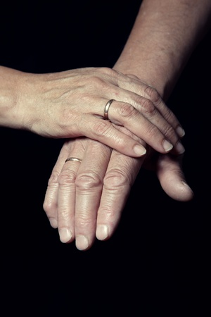 Hands of two loving senior people on a dark background photo