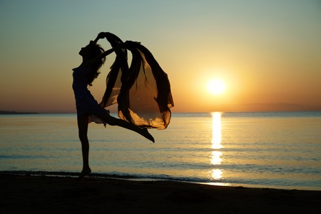 Silouette of the nifty woman dancing at the sea during sunset. Natural light and darkness. Artistic colors added Stock Photo