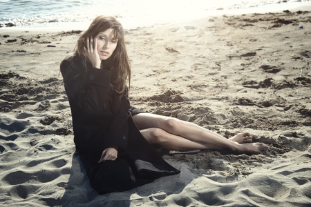 Sad woman in the black coat sitting on the sand at the autumn beach. Natural light and colors photo