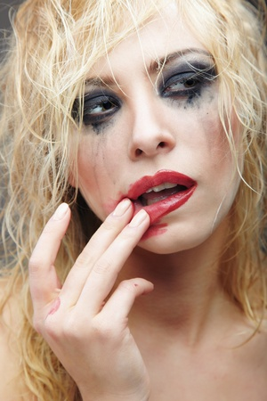 Beautiful blond lady with strange makeup smearing lipstick. Artistic colors added Stock Photo - 8987487