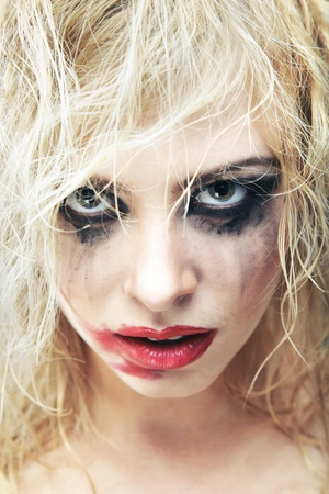 Blond lady with bizarre makeup and smeared lipstick on her face. Close-up photo. Natural colors Stock Photo - 8987489