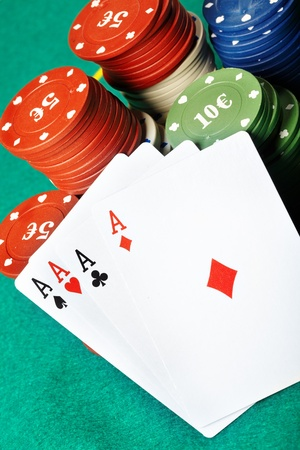 boodle: Set of four aces and poker chips on a green table Stock Photo