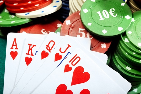 Royal flush and poker chips on a green table of casino