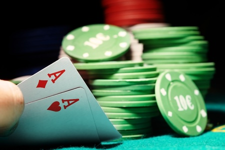gambling counter: Pair of aces and poker chips on a green table in casino Stock Photo