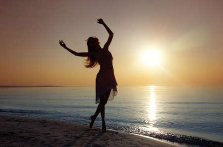 nifty: Silouette van de handige vrouw dansen op de zee tijdens zonsondergang. Natuurlijk licht en duisternis. Artistieke kleuren die zijn toegevoegd