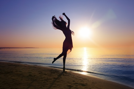 Silhouette of the woman dancing at the beach during beautiful sunset. Natural light and darkness. Artistic vivid colors added photo