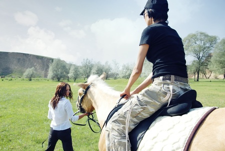 Lady riding on the horse with her trainer outdoors. Natural light and colors photo