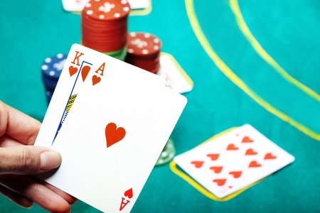 boodle: Human hand holding two cards in casino. Poker chips on a background