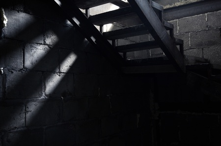 enigma: Old staircase in the dark basement. Natural light and shadows Stock Photo