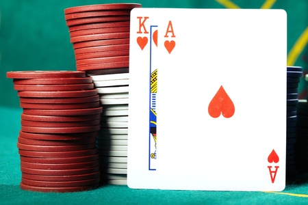 boodle: King and ace placed near the poker chips on a green table in casino. Close-up photo with natural colors Stock Photo
