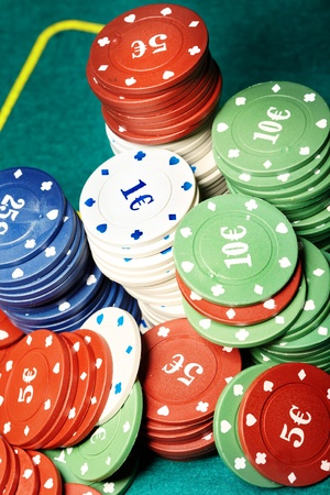 vehemence: Stack of casino chips on a green casino table. Close-up photo