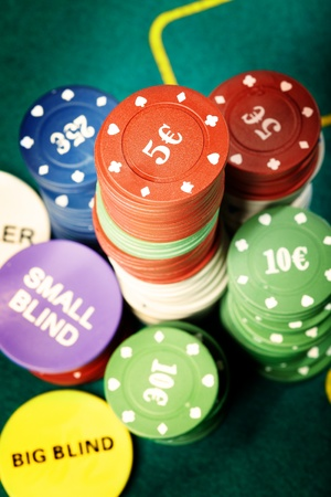 boodle: Stack of poker chips on a green table of casino