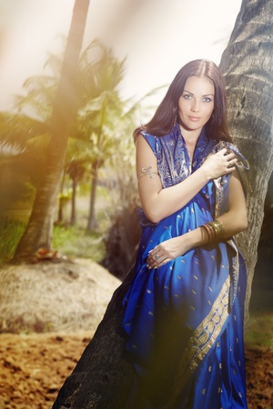 indian summer: Beautiful lady outdoors in the stylish sari posing in the wild jungle under the summer sunshine Stock Photo