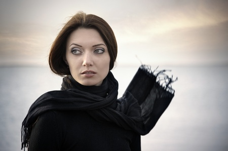 Romantic woman in black clothes with blown scarf outdoors at the sea photo