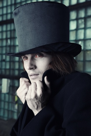 Vampire man with bloody eyes in the black coat and top hat indoors. Natural makeup colors
