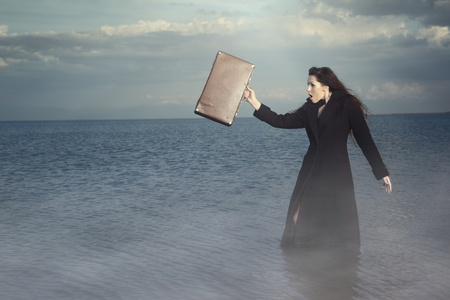 Bizarre female traveller with bag standing in the water with fog. Natural light and colors photo