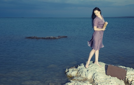 Romantic lady holding book and standing on the rock above the sea. Natural light and colors Stock Photo - 9309658