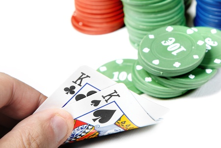 boodle: Pair of kings in human hand and poker chips on a white background