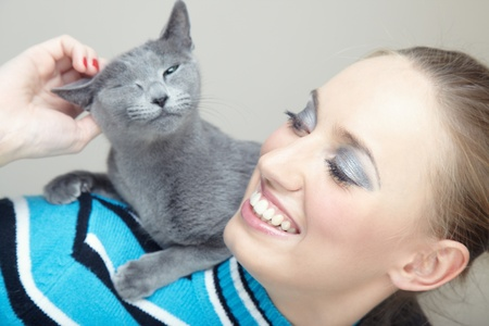 pamper: Smiling woman holding and pampering cat indoors