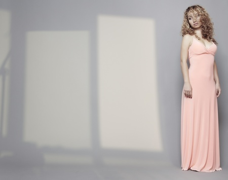 Woman in pink dress with curly hairs standing alone in the interior with shadows photo