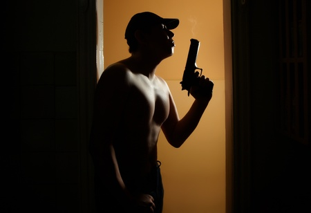Silhouette of the muscular man with fuming gun in the dark interior with orange walls Stock Photo - 9367189