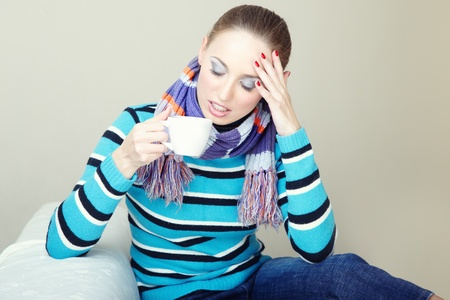 Sick woman with headache and high temperature holding cup with drug photo