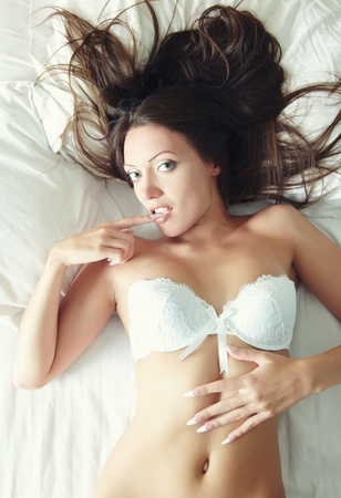 Sexy lady with white camisole laying and pampering on the bed. Natural light and colors photo
