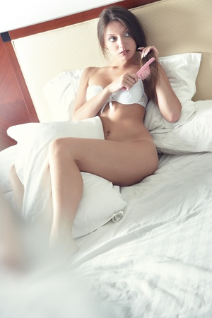 Elegant lady laying on the bed and combing her hairs. Natural light and colors Stock Photo - 9399818