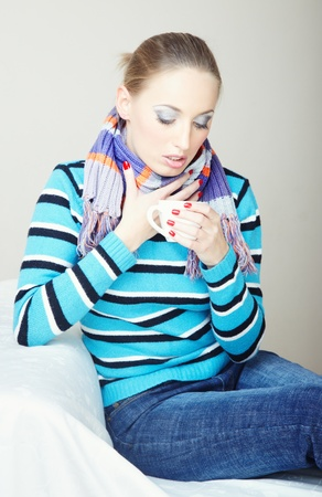 Sick woman in sweater and scarf holding cup with drugs Stock Photo - 9450420