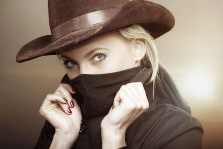 stetson: Criminal woman with cowboy hat during hot sunset. Creative colors added for movie effect