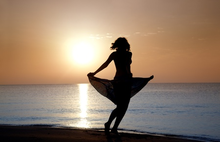 shadowgraph: Silhouette of the woman in dress moving at the beach during sunset. Natural darnkess and colors