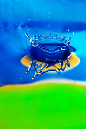 splutter: Macro photo of the liquid splash forming crown. Colors are blue yellow and green Stock Photo