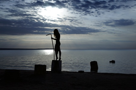 incubus: Silhouette of the female witch standing near the water during dark sunset