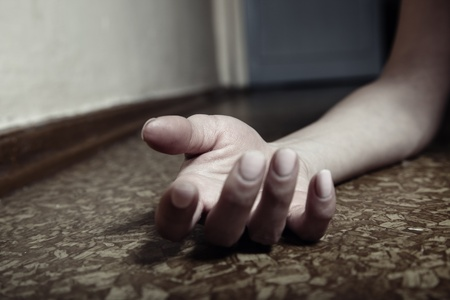 Close-up photo of the human hand laying on the floor