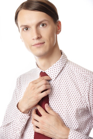 knotting: Successful businessman knotting red necktie on a white background