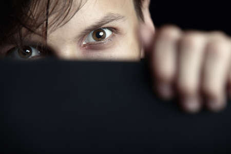 Evil man hides behind the black board and observes Stock Photo - 10024033