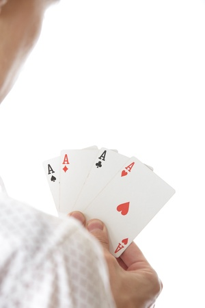 Man holding cards with Four of Aces. Rear view on a white background. Focus is on cards photo