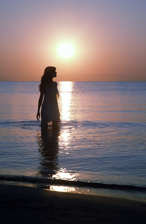 Silhouette of happy woman standing in the water at the beach during twilight photo