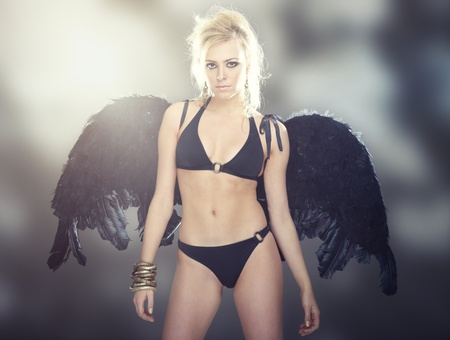 Blond female angel with black wings on abstract background photo