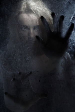 Female witch behind the dark glass photo