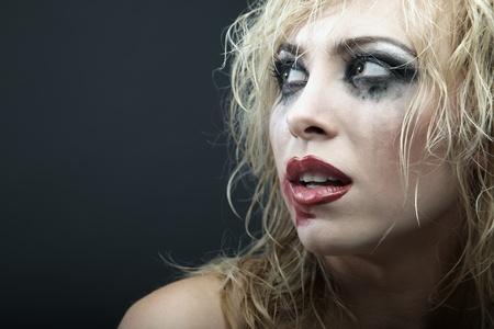 Crazy blond lady with bizarre makeup. Horizontal portrait