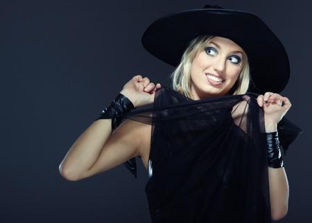 mujer pirata: Dama sonriente en el Halloween bruja traje sobre un fondo oscuro